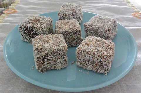 Lamingtons, ou bolo de baunilha com calda de chocolate e côco ralado.